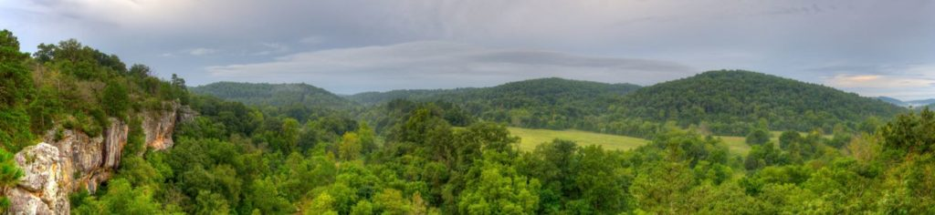 A panoramic view from atop Arkansas bluffs overlooking beautiful hilly green fields and woodlands
