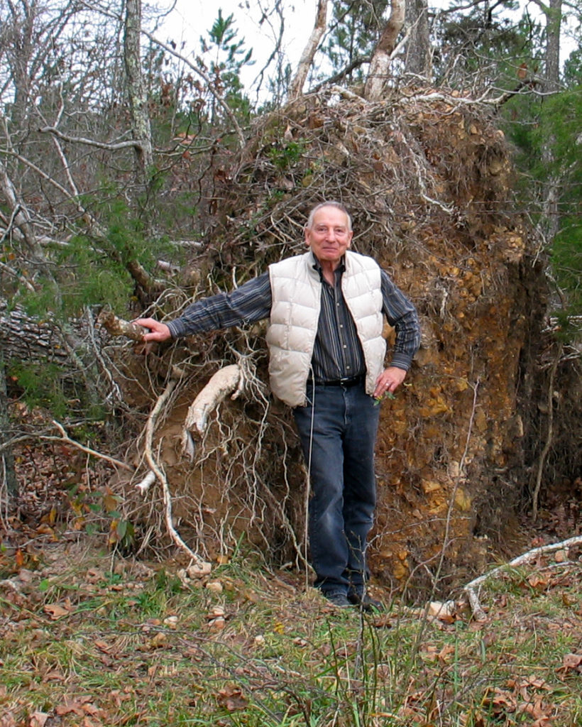 Dave Hartig stand next to a large uprooted tree