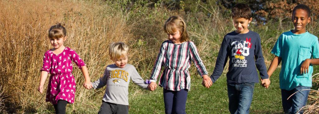 children-hold-hands-an-walk-a-green-path
